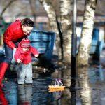 Женщина и ребенок запускают кораблик