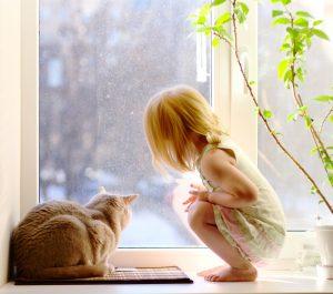 Девочка и кошка у окна
