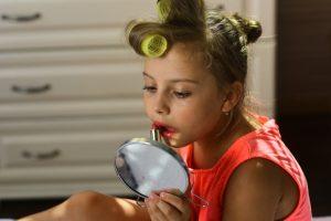 Девочка наносит макияж