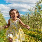Девочка бежит мимо яблонь
